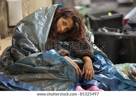 poor girl in city sitting in street near bin - stock photo