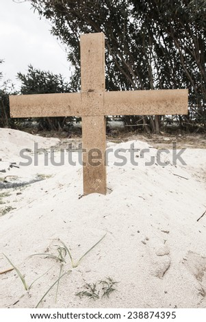 Poor grave in the sand with a wooden cross. Concept for human death. - stock photo