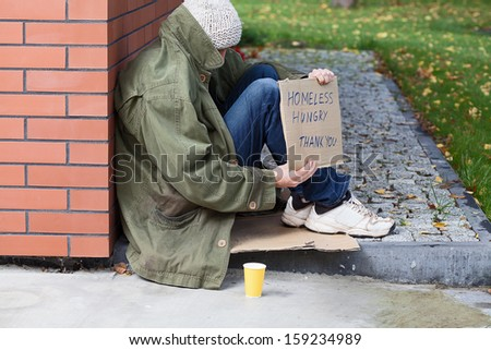 Poor homeless begging for money on a street - stock photo