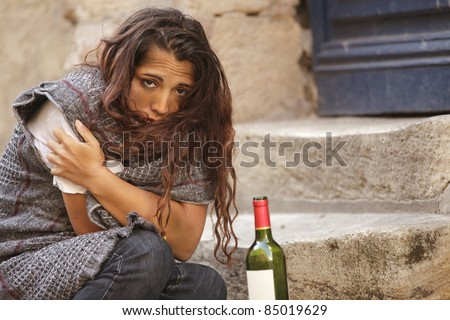 poor homeless drunk woman in cold weather - stock photo