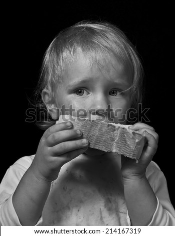 poor hungry child eating bread, black and white portrait on black - stock photo