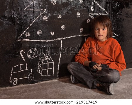 Poor kid at Christmas time on the street - sitting alone - stock photo