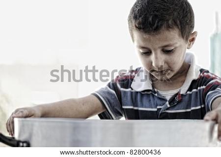 Poor kid looking in empty food pot - stock photo