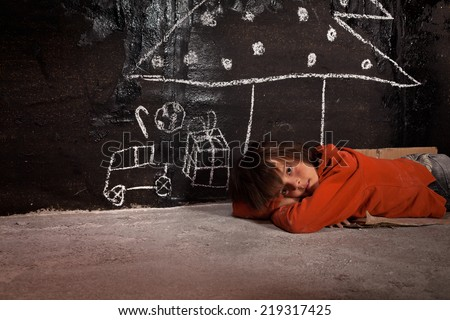 Poor kid on the street thinking of Christmas gifts - laying on the ground - stock photo