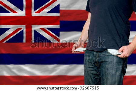 poor man showing empty pockets in front of american state of hawaii flag