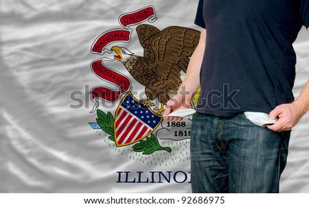 poor man showing empty pockets in front of american state of illinois flag - stock photo