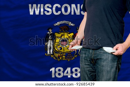 poor man showing empty pockets in front of american state of wisconsin flag - stock photo