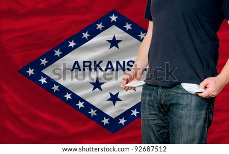 poor man showing empty pockets in front of arkansas flag