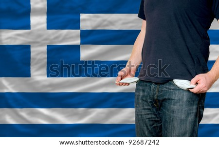 poor man showing empty pockets in front of greece flag - stock photo