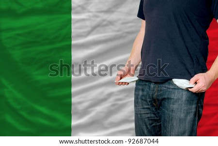 poor man showing empty pockets in front of italy flag - stock photo