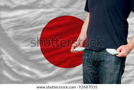 poor man showing empty pockets in front of japan flag - stock photo