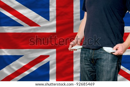 poor man showing empty pockets in front of uk flag - stock photo