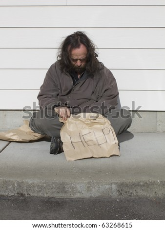Poor man sitting on sidewalk with help sign - stock photo