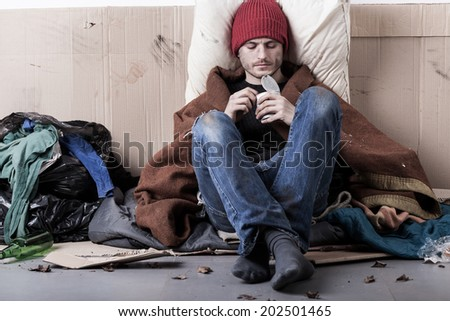 Poor man sitting on the street and eating preserve - stock photo
