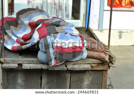 Poor man sleeping in the street in Varanasi - stock photo