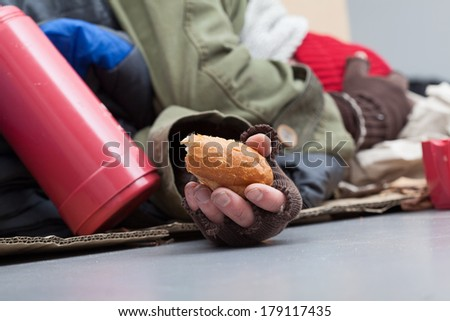 Poor man with piece of bread sleeping on a street - stock photo
