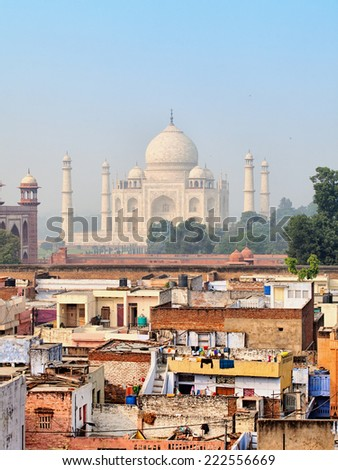 Poor neighborhoods of the city and luxurious Taj Mahal. Agra, India - stock photo
