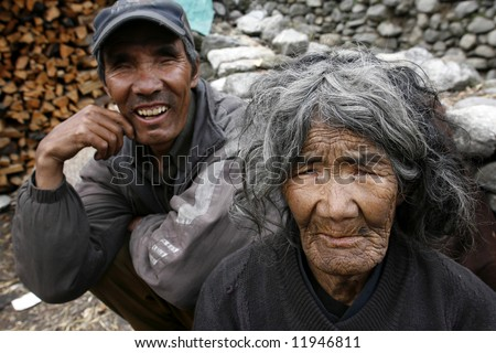 poor old lady and her blind son, annapurna, nepal - stock photo