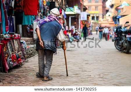 Poor old man walking with stick in exotic asian street, Nepal - stock photo