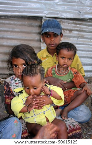 Poor sick chilren sitting on the sides of a street, in India. - stock photo