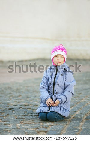 Poor unhappy girl-preschooler asks for alms in town square. - stock photo