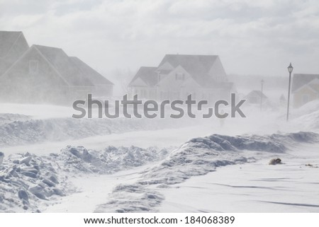 Poor visibility with strong winds blowing snow around during a snow storm in suburbia. - stock photo