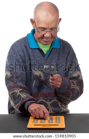 Poor vision forces an old man to see a calculator with the aid of glasses and magnifying glass. - stock photo