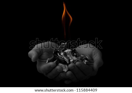 Poor worker holding a pack of dollars in fire - stock photo