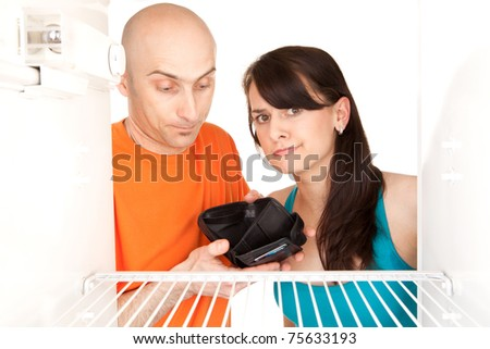 Poor young couple with no money looking in empty refrigerator. - stock photo