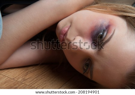 Poor young fair-haired woman with the black eye lying on the floor reassuring herself that everything will be ok - stock photo
