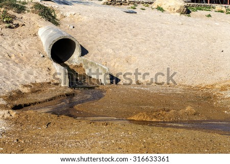 Poorly Treated wastewater is discharged into sea on coast in area of  beach. Environmental pollution. Violation of sanitary norms. Bathing is prohibited. The danger for people. Odessa, Ukraine, 2015 - stock photo