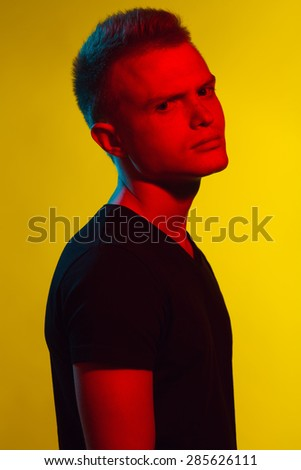 Pop-art style concept. Portrait of brutal young man with short hair wearing black t-shirt and posing over yellow background. Hipster style. Close up. Studio shot - stock photo