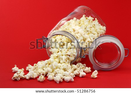 pop corn coming out of a glass jar on a red background - stock photo