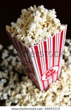 Pop corn container full of pop corn on black background - stock photo