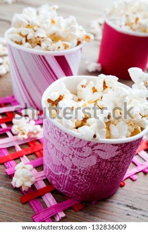 Pop corn in pink carton cups, selective focus - stock photo