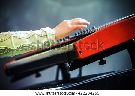 Pop music. Electric piano player hand and keyboard, closeup photo with selective focus - stock photo