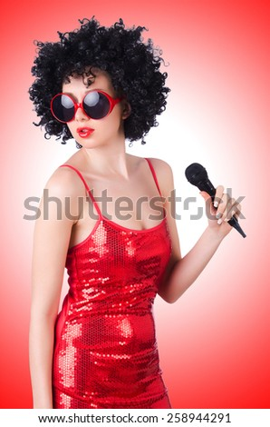 Pop star with mic in red dress on white - stock photo