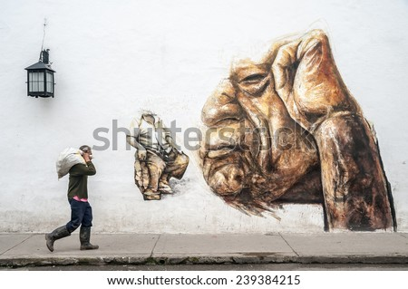 POPAYAN, COLOMBIA - NOVEMBER 9:  A man on a street on November 9, 2011  in Popayan, Colombia.  White buildings in the city often have graffiti drawings on their walls. - stock photo