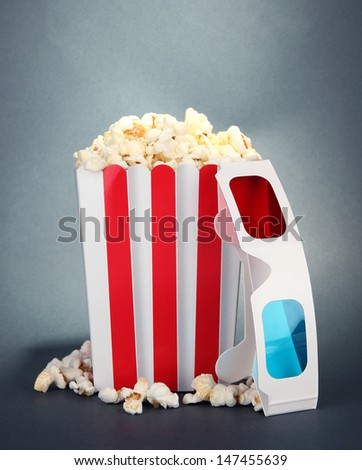 Popcorn and 3D glasses on grey background
