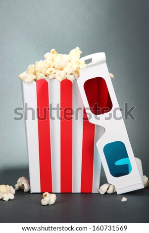 Popcorn and 3D glasses on grey background - stock photo