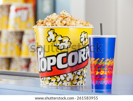 Popcorn bucket and cold drink on cinema concession stand - stock photo