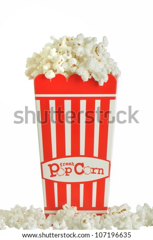 Popcorn container overflowing with tasty popcorn against a white background - stock photo