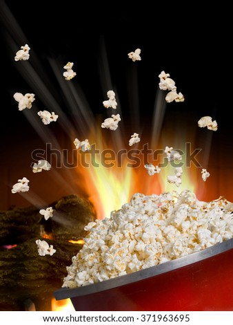 Popcorn flying and exploding from red kettle. - stock photo