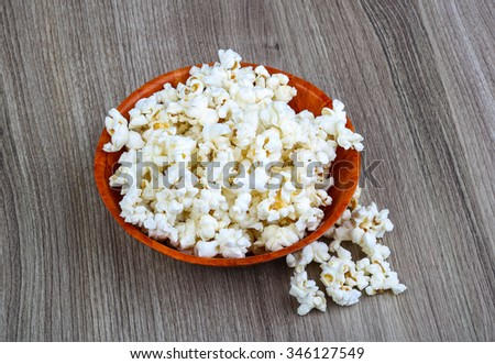 Popcorn heap in the bowl on wood background - stock photo