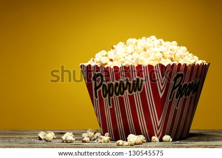 Popcorn in a container on a the yellow background. - stock photo