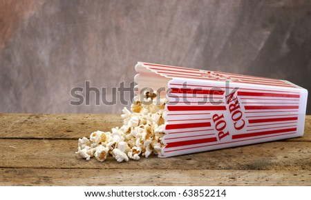 Popcorn in a container ready for the movies or your next project, on Old vintage wood table top with tan muted background. - stock photo