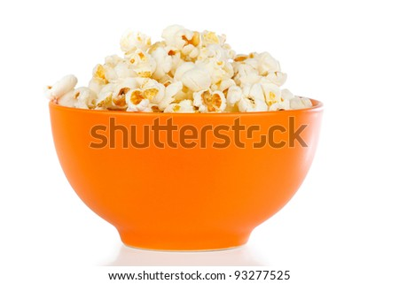 Popcorn in a orange bowl on a white background - stock photo
