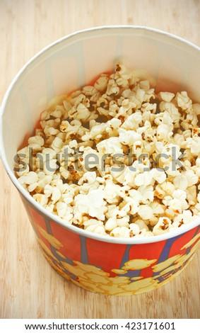 Popcorn in big paper bucket top view selective focus - stock photo
