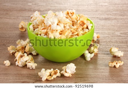 popcorn in bright plastic bowl on wooden table - stock photo