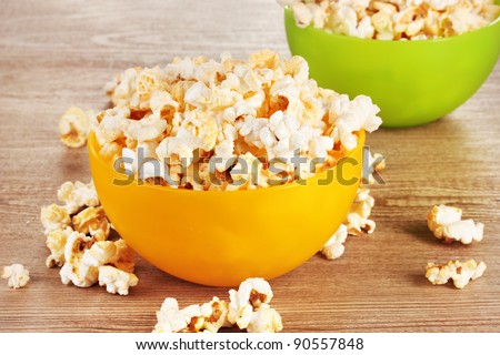 popcorn in bright plastic bowls on wooden table - stock photo